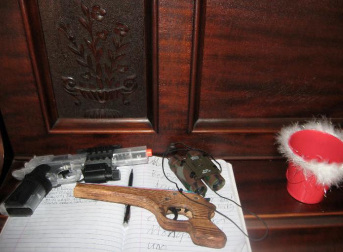 xmas list notebook, bimcoulars, and guns on piano